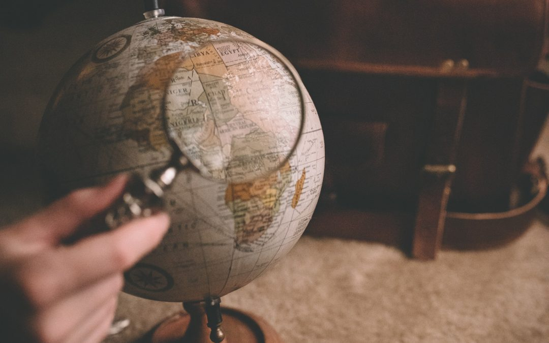 Magnifying glass over a globe with a leather briefcase | People Locator Service | Lake Oswego Private Investigators